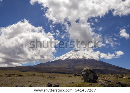 The snowcapped Cotopaxi Volcano in the Ecuadorian Andes with a lichen encrusted boulder in the foreground. Vapour is rising from the crater.