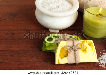 the soap and towel next to sea salt and candle on wooden background - stock photo