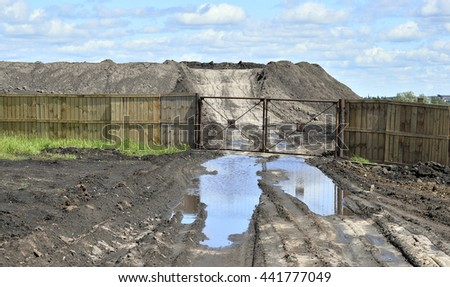 The soil is stored in the open air outside the fence on the background of a dirt road with a puddle of water