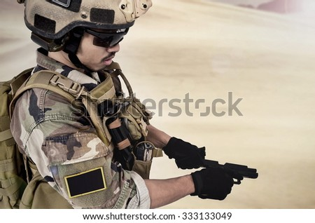 The soldier in full gear reload a gun at desert - stock photo