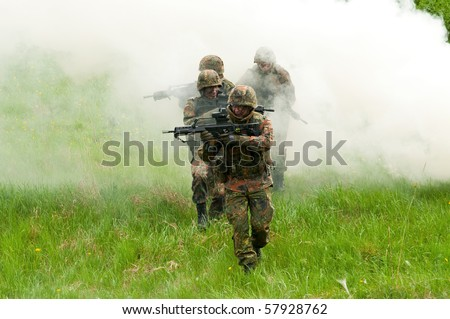 The soldier of the Bundeswehr in the zone of military operations. In the smoke. - stock photo