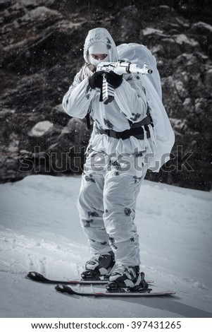 The soldier on skis and with a gun. Skiing down the mountain - stock photo