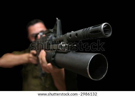 The soldier with the automatic weapon equipped by a grenade cup discharge - stock photo