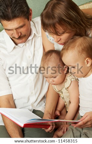 The son and daughter with mother and father read the interesting book - stock photo