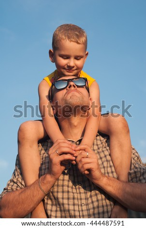 the son from his father under a beautiful sky, a boy plays with dad, the child tries on sunglasses - stock photo