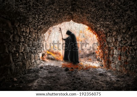 The sorcerer with the robe in a dark cavern - stock photo