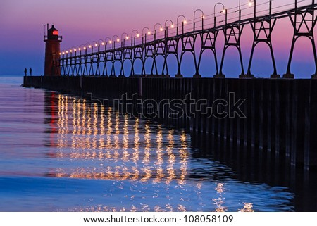 The South Pierhead Light in South Haven, Michigan after Sundown with lights reflecting on Lake Michigan waves - stock photo