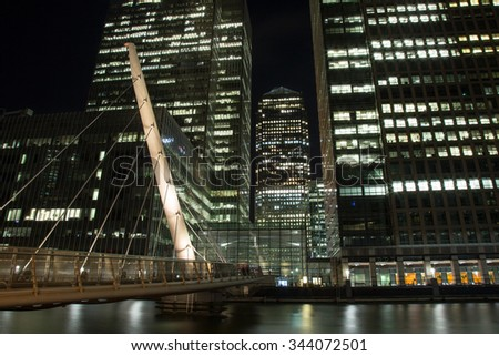 The South Quay Footbridge leading to the financial district Canary Wharf, London by night - stock photo