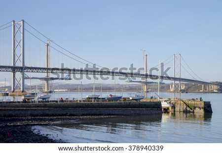 The South Queensferry side of the Forth Road Bridge, with two partially-completed towers of the new Queensferry Crossing Bridge in the background. South Queensferry Harbour is in the foreground. - stock photo