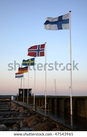 The southern harbour pier in Elsinore Harbour at sunset with Nordic and European flags. - stock photo