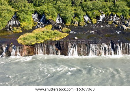 The spectacular Hraunfossar cascades, a waterfall in Iceland, where natural springs supply the water from the rhyolite mountains, covered with shrubs, bushes, grass and moss. - stock photo