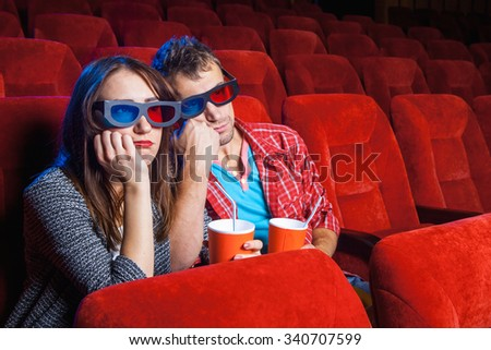 The spectators sitting in the cinema and watching movie  with cups of cola and popcorn. Concept of a variety of human emotions.