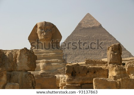 the Sphinx sits in front of the great pyramid at Giza in Egypt, just outside of Cairo. - stock photo
