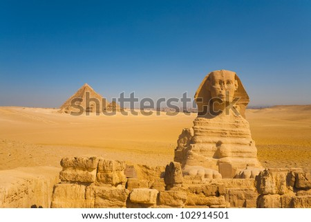 The sphinx stands guard to a distant set of Giza pyramids in a vast desert with the city of Cairo in the background, Egypt - stock photo