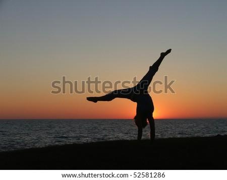the splits on beach in sunset - stock photo
