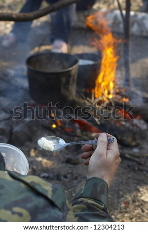 The spoon with rice on a background of a tourist fire on a halt