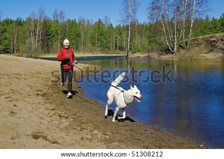 The sports woman with a dog run along coast of the rivers - stock photo