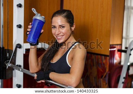 The sports young woman with a protein cocktail in a shaker stands in a gym. Sports nutrition. - stock photo