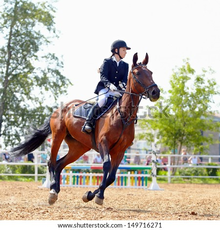 The sportswoman on a horse. The horsewoman on a red horse. Equestrianism. Horse riding. Horse racing. Rider on a horse. - stock photo