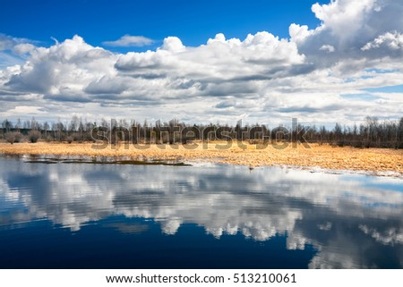 The spring sky with the clouds, reflected in quiet water of lake, Siberia, Russia