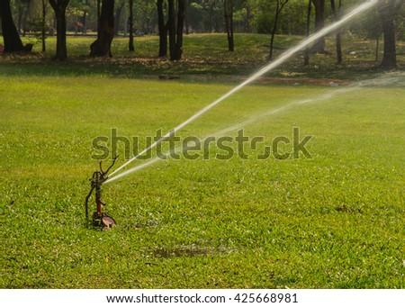 The sprinkler in the park. - stock photo