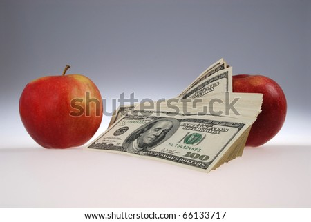 The stack of dollars lays near two apples. On grey background. - stock photo