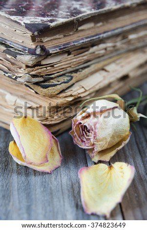 The stack of old books and dried rose lying on an old wooden board - stock photo