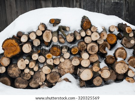 the stack of the snowy firewood on old wooden background. A horizontal outdoor photo  - stock photo