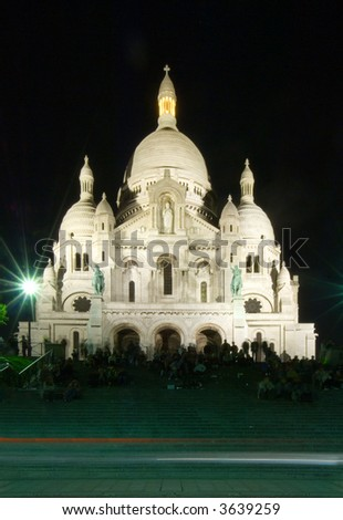 The staircase of the Sacre  Coeur in Montmartre, filled with people watching over the Parisian skyline at night, and enjoying the entertainment provided by street artists. Cars driving by - stock photo