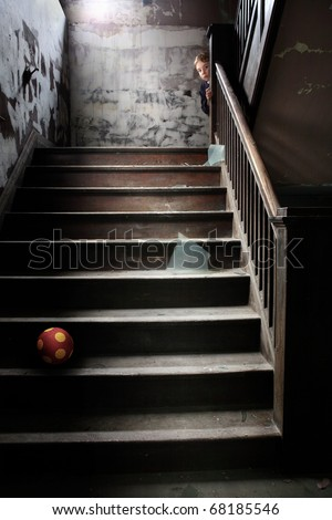 The Stairwell, a child peeks around the corner of the banister at the stairs littered with broken glass and a ball - stock photo