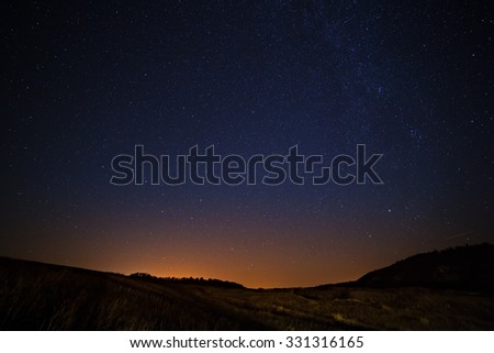 The starry sky and Milky Way  above the lighted lanterns city.