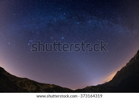 The starry sky and Milky Way captured on the Alps by fisheye lens with scenic distortion and 180 degree view. Andromeda, The Pleiades, Orion and Sirio clearly visible. Low digital noise. - stock photo
