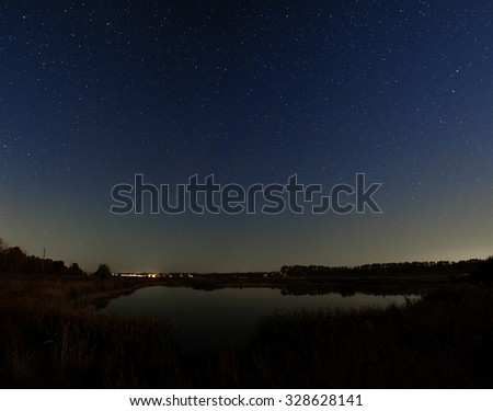 The stars in the night sky. Night landscape with a smooth surface of the river. - stock photo