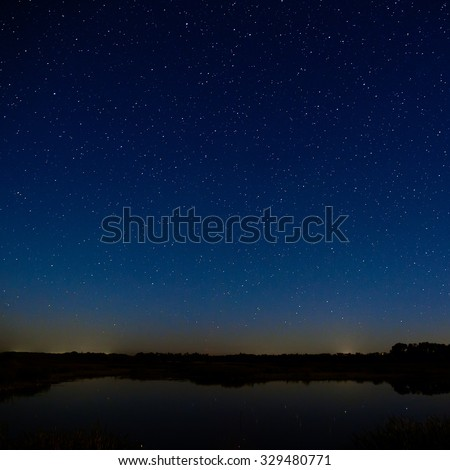 The stars in the night sky. Night landscape with a smooth surface of the river.