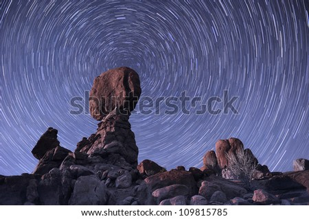 The stars spin around the balance rock formation at Arches National Park, USA