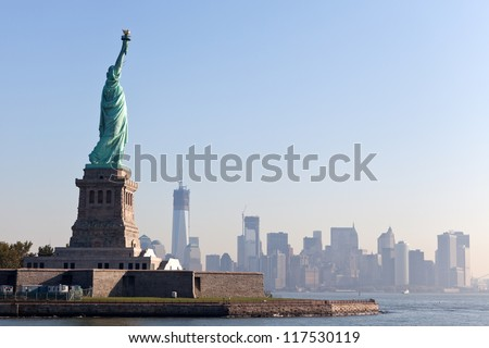 The Statue of Liberty free of tourists and New York City Downtown on sunny early morning - stock photo