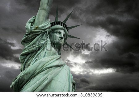The Statue of Liberty in New York, a detail of the head with stormy clouds, USA - stock photo