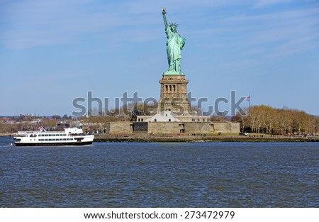 The Statue of Liberty lit by the early morning sunrise - stock photo