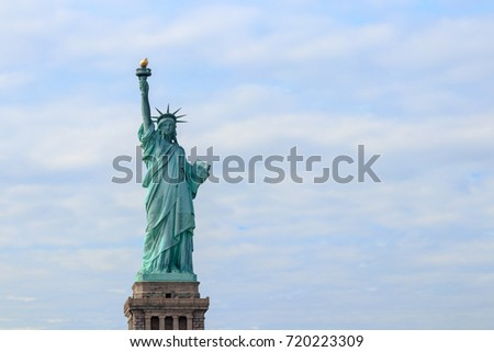 The Statue of Liberty on Liberty Island in New York City. It is the copper statue which is a gift from the people of France to the United States. She holds a torch above her head.