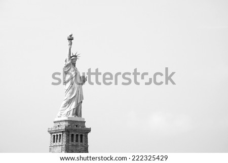 The Statue of Liberty stands proudly against a clear sky - monochrome processing - stock photo