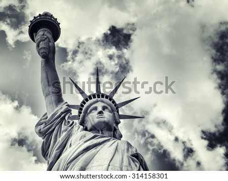 The Statue of Liberty with a dramatic cloudy sky - stock photo