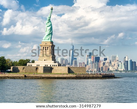 The Statue of Liberty with the New York skyline on the background on a beautiful summer day - stock photo