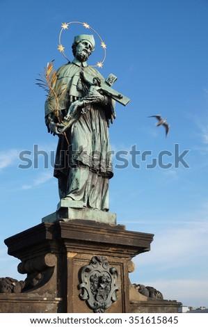 The Statue of St. John of Nepomuk at the Charles Bridge in Prague - stock photo
