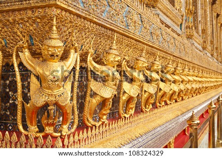 The statues of Garuda battling naga serpent on the wall of temple in Thailand