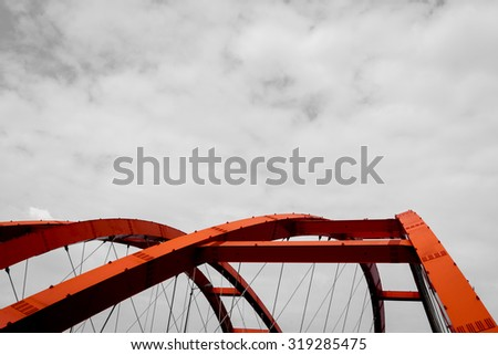 The steel construction of red bridge on a monochromatic background  - stock photo