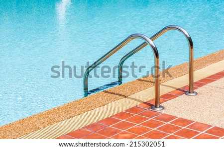 The steel ladder of swimming pool in summer time - stock photo
