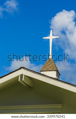 The steeple and cross on the roof of a small chapel