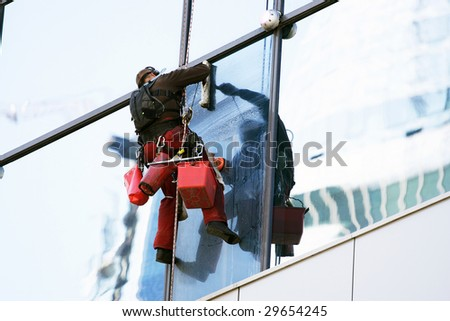 The steeplejack washes windows of a high-rise building - stock photo