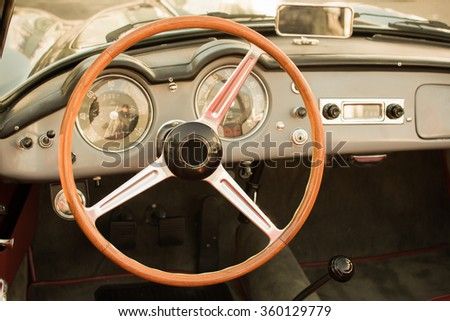 The steering wheel and dashboard of an antique classic car - stock photo