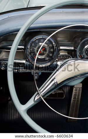 The steering wheel and dashboard of an antique classic car. - stock photo